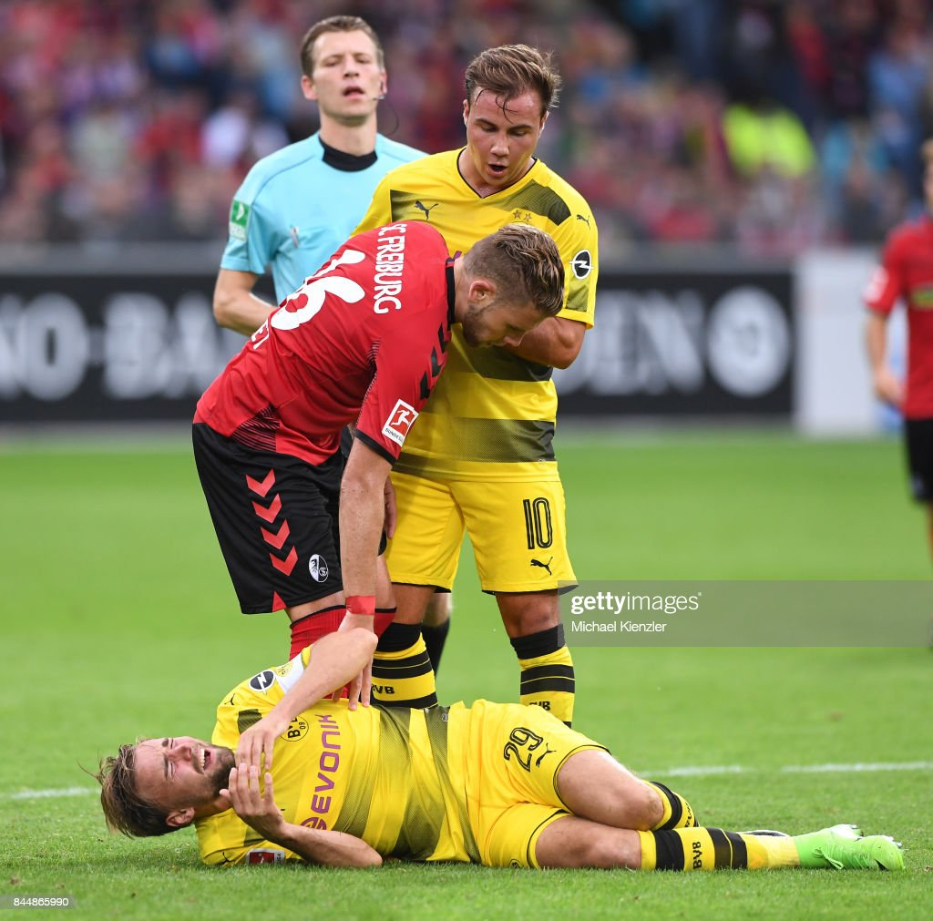 Marcel Schmelzer of Borussia Dortmund laying injured on pitch, tackled by Yoric Ravet (L) of SC Freiburg during the Bundesliga match between Sport Club Freiburg and Borussia Dortmund at Schwarzwald-Stadion on September 9, 2017 in Freiburg, Germany.