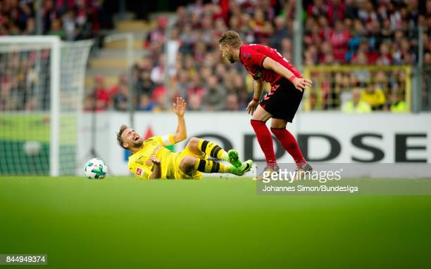 Marcel Schmelzer of Dortmund is fouled by Yoric Ravet of Freiburg during the Bundesliga match between SportClub Freiburg and Borussia Dortmund at...