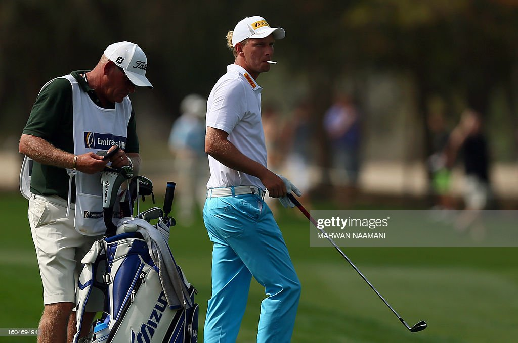 Marcel Seim of Germany smokes a cigarette during the second round of the Dubai Desert Classic golf tournament in the Gulf emirate of Dubai on February 1, 2013.