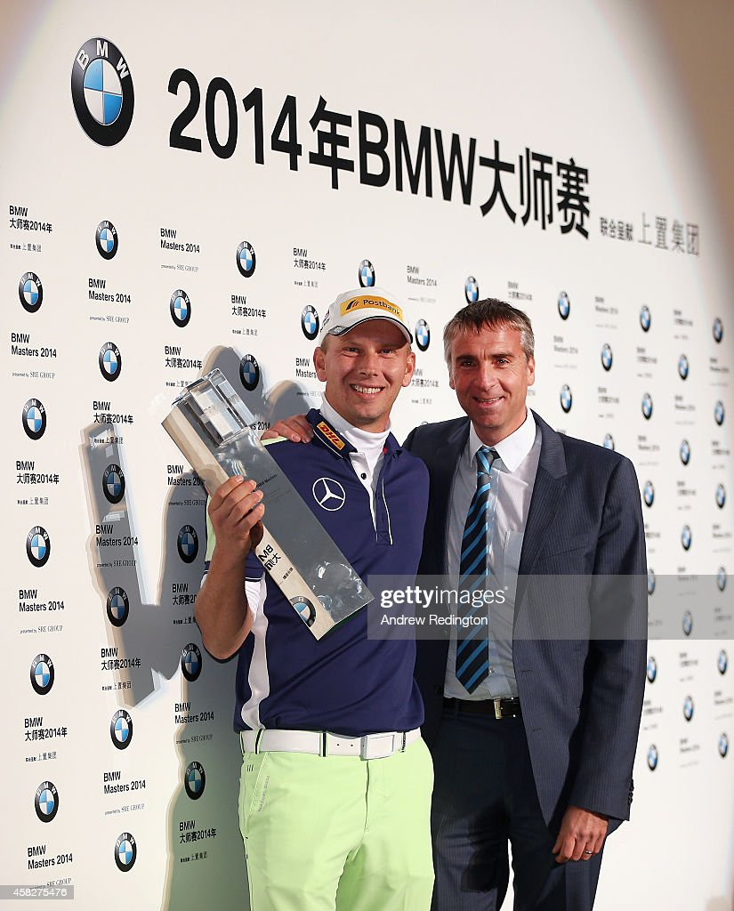 Marcel Siem of Germany poses with the trophy with Tournament Director Marco Kaussler after winning the BMW Masters at Lake Malaren Golf Club on...