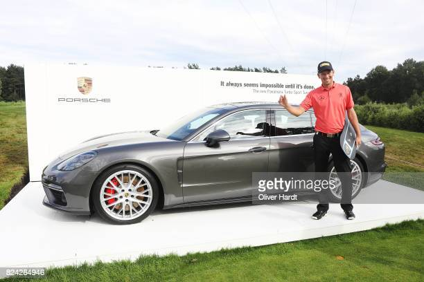 Marcel Siem of Germany receive his price Porsche Panamera Sport Turismo after making a hole in one on the 17th hole during the Green Eagle Golf...