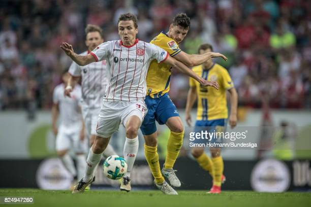 Marcel Sobottka of Duesseldorf is tackled by Quirin Moll of Braunschweig during the the Second Bundesliga match between Fortuna Duesseldorf and...