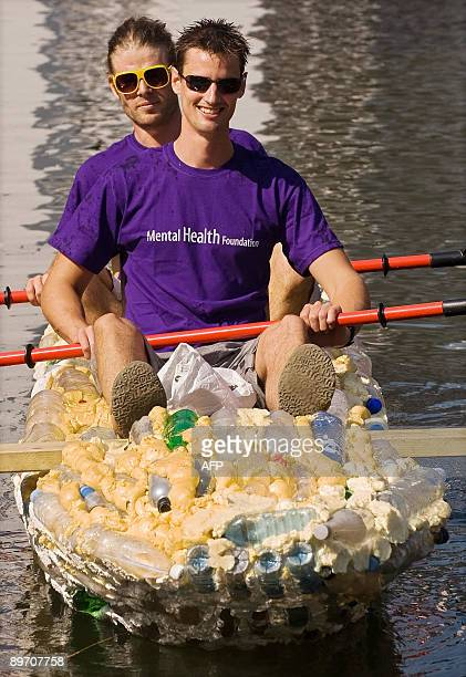 Marcel Syron and Cameron Holm pose for photographs on August 8 2009 at Camden Lock in North London on their boat made out of plastic bottles ahead of...