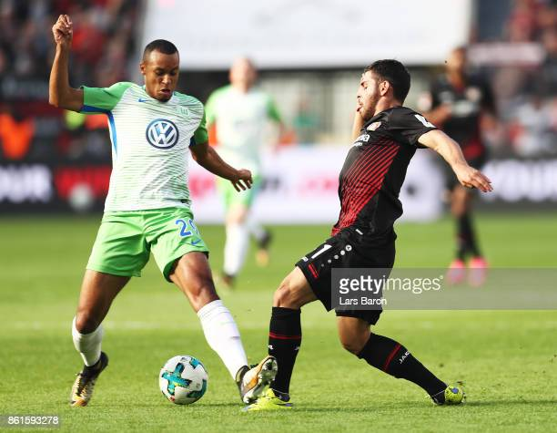 Marcel Tisserand of VfL Wolfsburg is challenged by Kevin Volland of Bayer Leverkusen during the Bundesliga match between Bayer 04 Leverkusen and VfL...