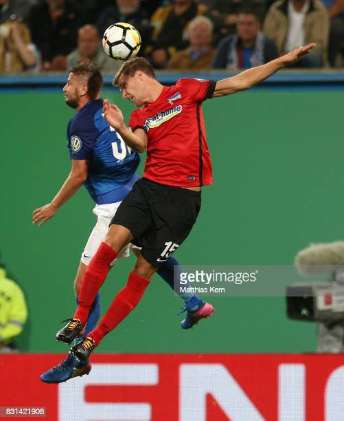 Marcel Ziemer of Rostock and Sebastian Langkamp of Berlin jump for a header during the DFB Cup first round match between FC Hansa Rostock and Hertha...