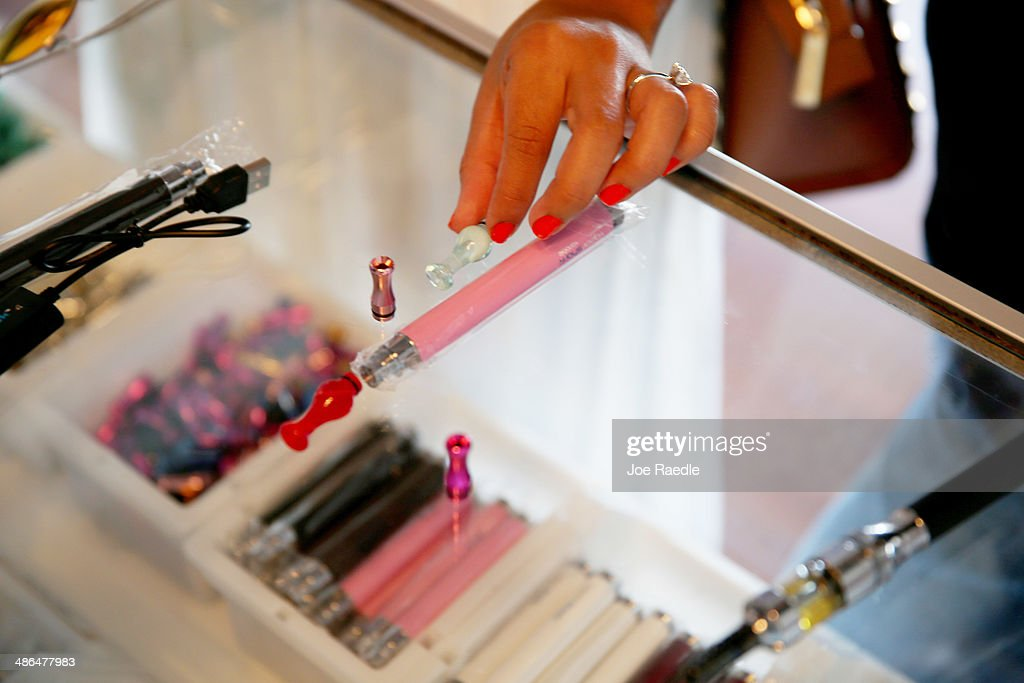 Marcela Guerra purchases an electronic cigarette at the Vapor Shark store on April 24, 2014 in Miami, Florida. Brandon Leidel, CEO, Director of Operations Vapor Shark, said he welcomes the annoucement by the Food and Drug Administration that they are proposing the first federal regulations on electronic cigarettes, which would ban sales of the popular devices to anyone under 18 and require makers to gain FDA approval for their products.