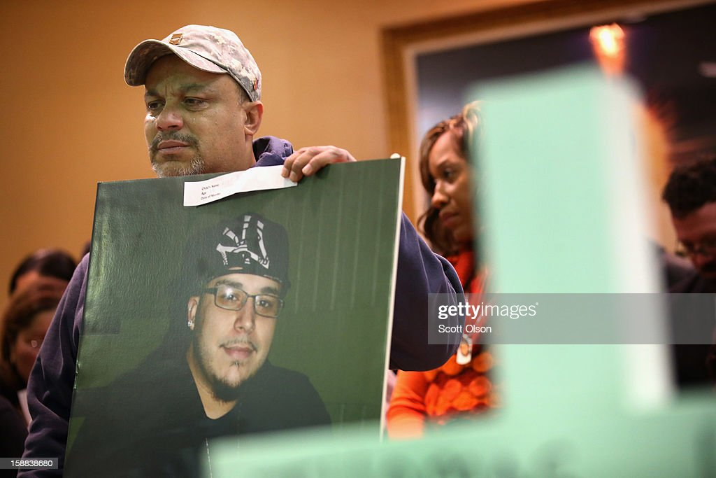 Marcelino Diaz weeps while he holds a picture of his son Lino during a press conference he attended with other family members of murder victims on December 31, 2012 in Chicago, Illinois. Lino was 23-years-old when he was shot to death on May 25, 2012.