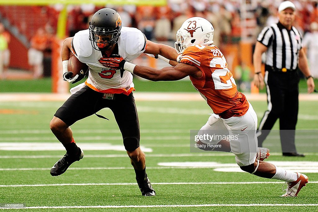 Marcell Ateman #3 of the Oklahoma State Cowboys tries to elude Carrington Byndom #23 of the Texas Longhorns during a game at Darrell K Royal-Texas Memorial Stadium on November 16, 2013 in Austin, Texas. Oklahoma State won the game 38-13.