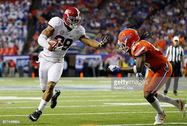 Marcell Harris of the Florida Gators tackles OJ Howard of the Alabama Crimson Tide in the first half during the SEC Championship game at the Georgia...