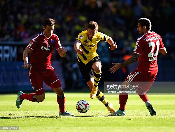 Marcell Jansen and Valon Behrami of Hamburger SV challenge Erik Durm of Borussia Dortmund during the Bundesliga match between Borussia Dortmund and...