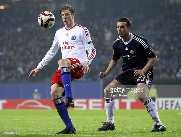 Marcell Jansen of Hamburg and Roland Juhasz of Anderlecht battle for the ball during the UEFA Europa League round of 16 first leg match between...
