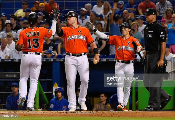 Marcell Ozuna and Justin Bour of the Miami Marlins celebrate with Derek Dietrich during the game against the Chicago Cubs at Marlins Park on June 25...