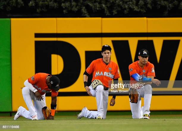 Marcell Ozuna Christian Yelich and Giancarlo Stanton of the Miami Marlins take a knee during an injury timeout in the fifth inning during the game...