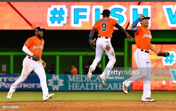 Marcell Ozuna Dee Gordon and Giancarlo Stanton of the Miami Marlins celebrate the win after the game between the Miami Marlins and the Colorado...