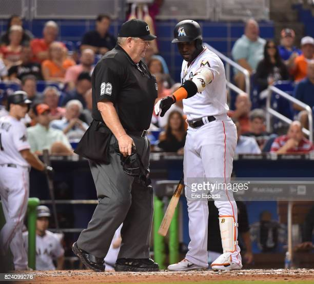 Marcell Ozuna of the Miami Marlins argues a call third strike with umpire Joe West during the third inning against the Cincinnati Reds at Marlins...