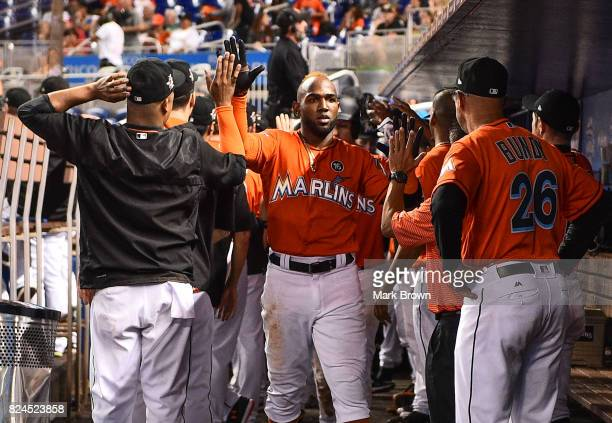 Marcell Ozuna of the Miami Marlins celebrated a homerun with teammates during the game between the Miami Marlins and the Cincinnati Reds at Marlins...