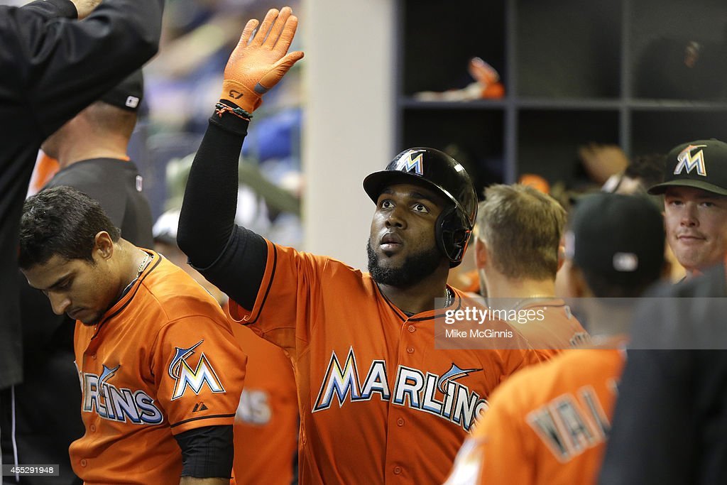 Marcell Ozuna #13 of the Miami Marlins celebrates in the dugout after hitting a two-run homer in the top of the eighth inning against the Milwaukee Brewers at Miller Park on September 11, 2014 in Milwaukee, Wisconsin.