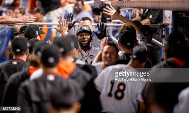 Marcell Ozuna of the Miami Marlins celebrates in the dugout during the game against the Atlanta Braves at Marlins Park on September 29 2017 in Miami...