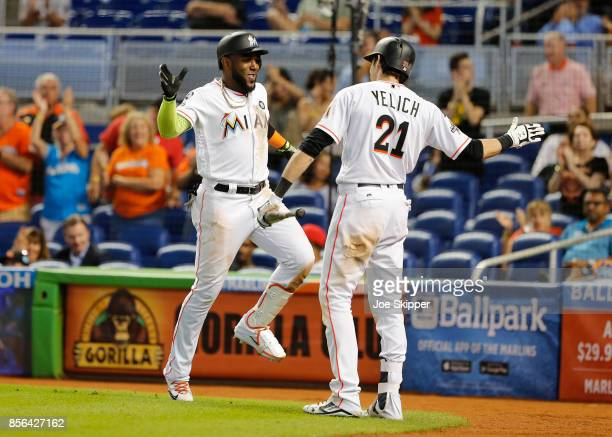 Marcell Ozuna of the Miami Marlins celebrates with teammate Christian Yelich after hitting a seventh inning solo home run against the Atlanta Braves...