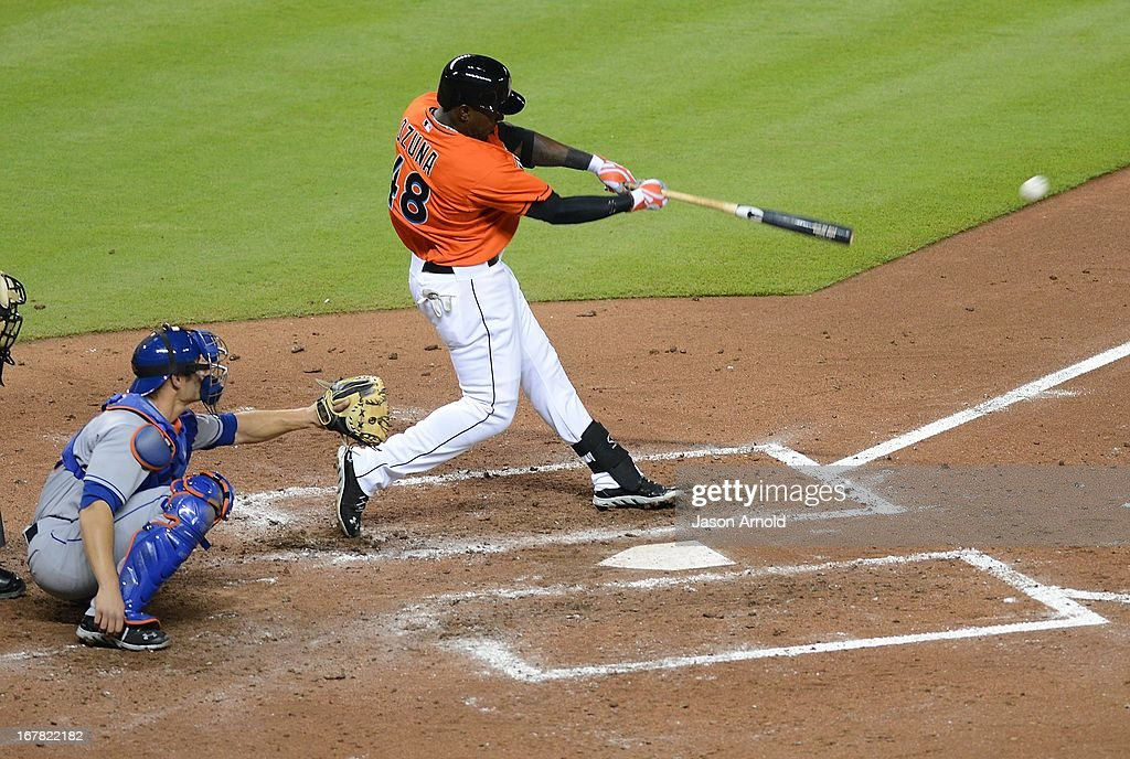Marcell Ozuna #48 of the Miami Marlins connects for a bse hit in front of catcher Anthony Recker #26 of the New York Mets at Marlins Park on April 30, 2013 in Miami, Florida.
