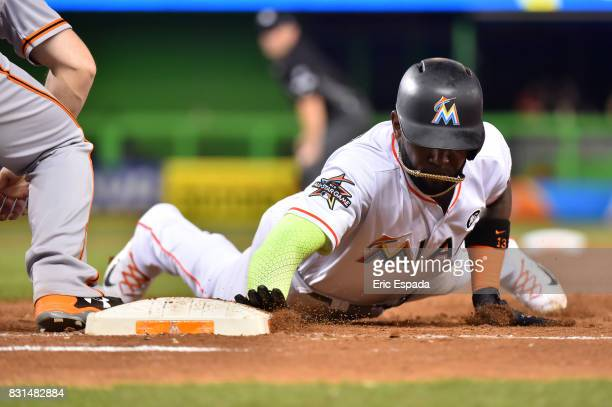 Marcell Ozuna of the Miami Marlins dives back to first base on a pickoff attempt during the seventh inning against the San Francisco Giants at...