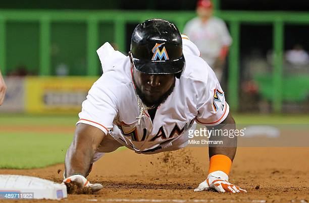 Marcell Ozuna of the Miami Marlins dives back to first during a game against the Philadelphia Phillies at Marlins Park on September 23 2015 in Miami...