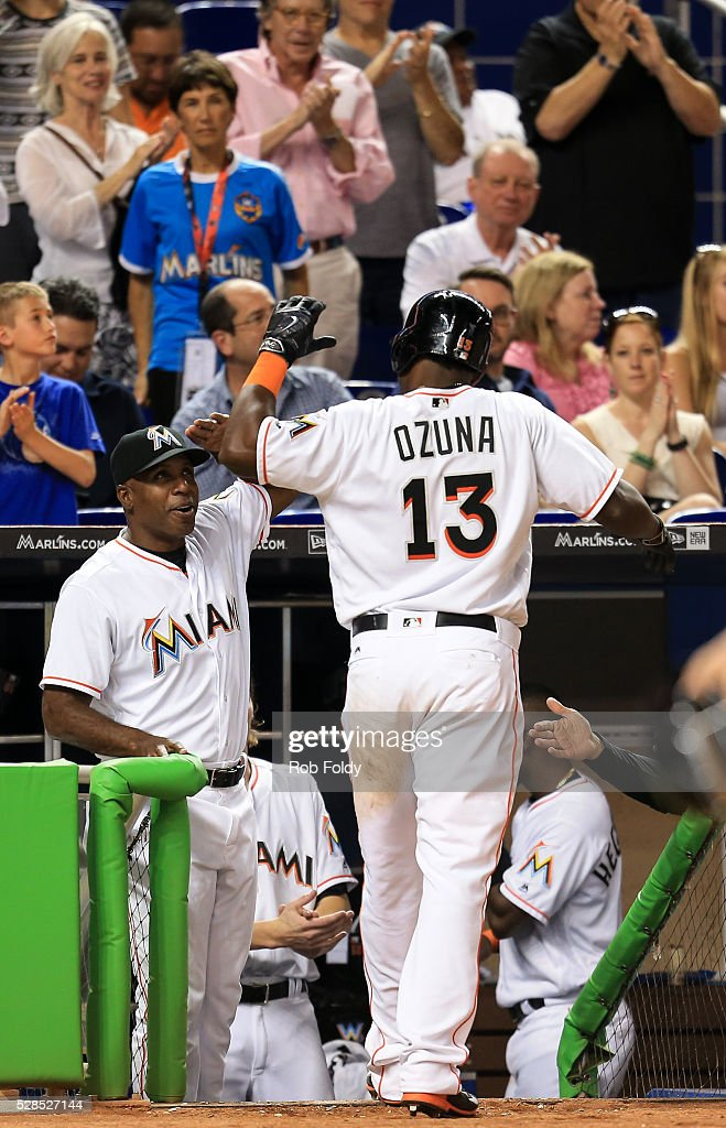 <a gi-track='captionPersonalityLinkClicked' href=/galleries/search?phrase=Marcell+Ozuna&family=editorial&specificpeople=10358366 ng-click='$event.stopPropagation()'>Marcell Ozuna</a> #13 of the Miami Marlins high-fives hitting coach <a gi-track='captionPersonalityLinkClicked' href=/galleries/search?phrase=Barry+Bonds&family=editorial&specificpeople=171194 ng-click='$event.stopPropagation()'>Barry Bonds</a> #25 after scoring a run during the fourth inning of the game against the Arizona Diamondbacks at Marlins Park on May 5, 2016 in Miami, Florida.