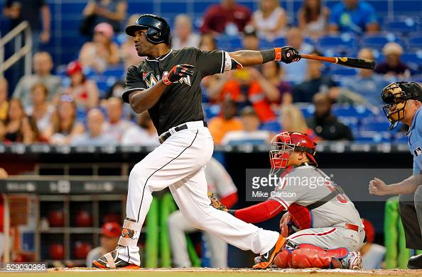 Marcell Ozuna of the Miami Marlins hits a home run in front of catcher Carlos Ruiz of the Philadelphia Phillies during the second inning of a game at...