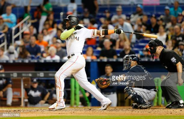 Marcell Ozuna of the Miami Marlins hits a seventhinning home run in front of Kurt Suzuki of the Atlanta Braves at Marlins Park on October 1 2017 in...