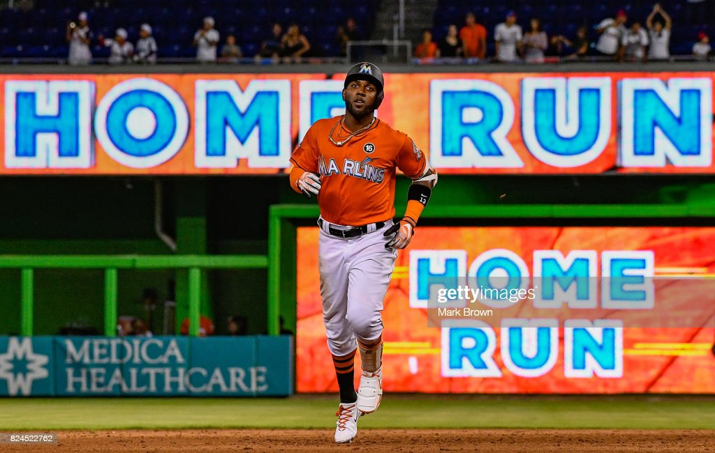 Marcell Ozuna #13 of the Miami Marlins hits a three run homerun in the ninth inning during the game between the Miami Marlins and the Cincinnati Reds at Marlins Park on July 30, 2017 in Miami, Florida.