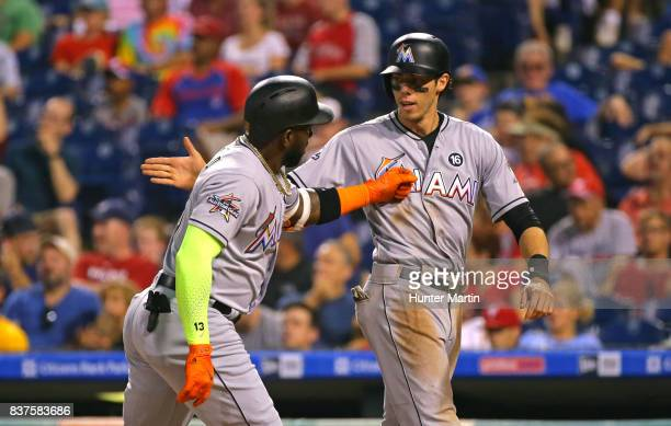 Marcell Ozuna of the Miami Marlins is congratulated at home plate by Christian Yelich after hitting a tworun home run in the first inning during game...