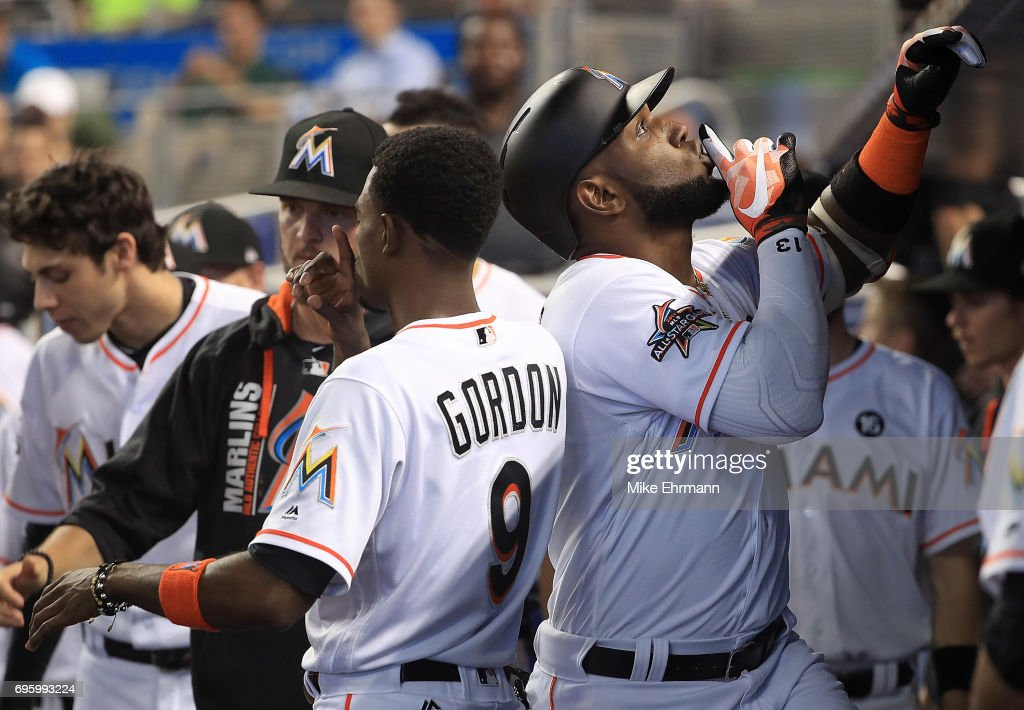 Marcell Ozuna #13 of the Miami Marlins is congratulated by Dee Gordon #9 after hitting a solo home run during a game against the Oakland Athletics at Marlins Park on June 14, 2017 in Miami, Florida.