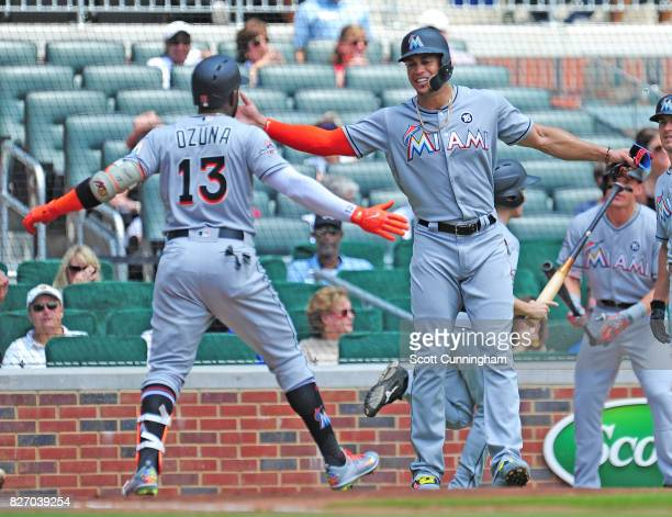 Marcell Ozuna of the Miami Marlins is congratulated by Giancarlo Stanton after hitting a first inning threerun home run against the Atlanta Braves at...