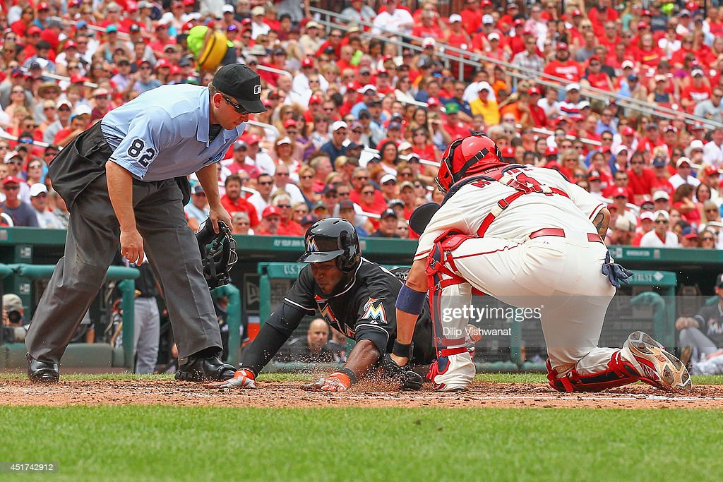 <a gi-track='captionPersonalityLinkClicked' href=/galleries/search?phrase=Marcell+Ozuna&family=editorial&specificpeople=10358366 ng-click='$event.stopPropagation()'>Marcell Ozuna</a> #13 of the Miami Marlins is tagged out at home plate by <a gi-track='captionPersonalityLinkClicked' href=/galleries/search?phrase=Yadier+Molina&family=editorial&specificpeople=172002 ng-click='$event.stopPropagation()'>Yadier Molina</a> #4 of the St. Louis Cardinals as umpire Clint Fagan #82 looks to make the call in the ninth inning at Busch Stadium on July 5, 2014 in St. Louis, Missouri. The Marlins beat the Cardinal 6-5.