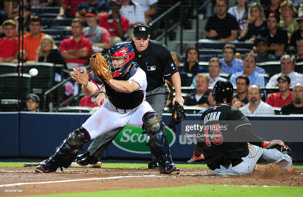 <a gi-track='captionPersonalityLinkClicked' href=/galleries/search?phrase=Marcell+Ozuna&family=editorial&specificpeople=10358366 ng-click='$event.stopPropagation()'>Marcell Ozuna</a> #13 of the Miami Marlins scores the go-ahead run in the ninth inning against <a gi-track='captionPersonalityLinkClicked' href=/galleries/search?phrase=Evan+Gattis&family=editorial&specificpeople=8977937 ng-click='$event.stopPropagation()'>Evan Gattis</a> #24 of the Atlanta Braves at Turner Field on July 24, 2014 in Atlanta, Georgia.