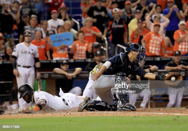 Marcell Ozuna of the Miami Marlins slides home in front of the tag from Kurt Suzuki of the Atlanta Braves during a game at Marlins Park on October 1...