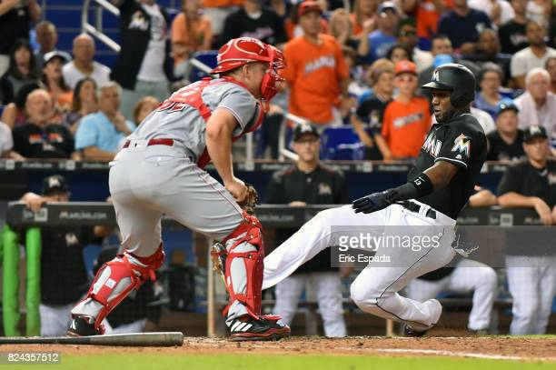 Marcell Ozuna of the Miami Marlins slides home safely on an RBI single by JT Realmuto in the seventh inning against the Cincinnati Reds at Marlins...