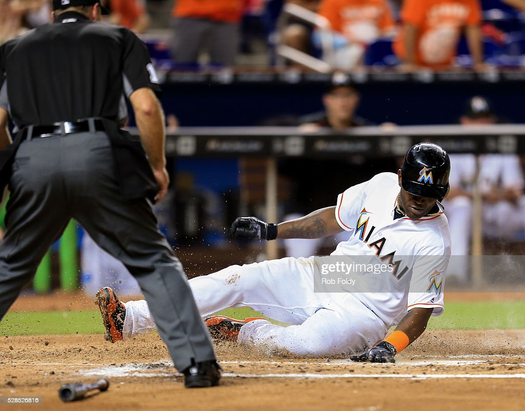 <a gi-track='captionPersonalityLinkClicked' href=/galleries/search?phrase=Marcell+Ozuna&family=editorial&specificpeople=10358366 ng-click='$event.stopPropagation()'>Marcell Ozuna</a> #13 of the Miami Marlins slides into home plate to score a run during the fourth inning of the game against the Arizona Diamondbacks at Marlins Park on May 5, 2016 in Miami, Florida.