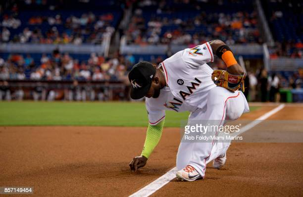 Marcell Ozuna of the Miami Marlins writes in the dirt before the game against the Atlanta Braves at Marlins Park on October 1 2017 in Miami Florida