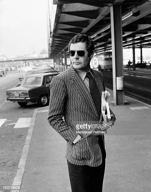 Marcello Mastroianni photographed out strolling with hand in pocket and dark glasses Milan 1971