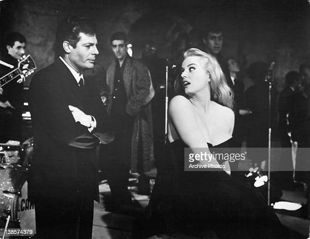 Marcello Mastroianni with his arms folded looking at Anita Ekberg in a scene from the film 'La Dolce Vita' 1960