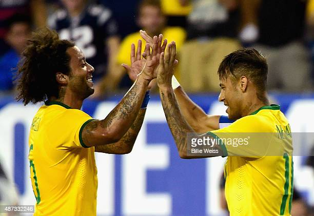 Marcelo and Neymar of Brazil react after Neymar scored a goal during an international friendly against the United States at Gillette Stadium on...