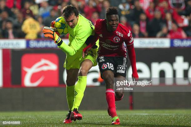 Marcelo Barovero goalkeeper of Necaxa struggles for the ball with Aviles Hurtado of Tijuana during the 6th round match between Tijuana and Necaxa as...