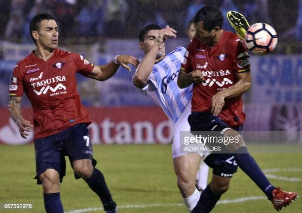 Marcelo Bergese and Omar Morales of Bolivia's Wilstermann vie for the ball with Fernando Evangelista Atletico Tucuman of Argentina during their Copa...