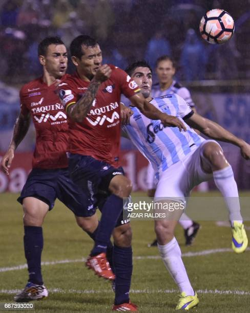 Marcelo Bergese and Omar Morales of Bolivia's Wilstermann vies for the ball with Fernando Evangelista Atletico Tucuman of Argentina during their Copa...