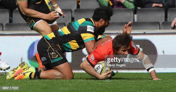 Marcelo Bosch of Saracens dives over for the last minute try despite being tackled by Ahsee Tuala during the Aviva Premiership match between...