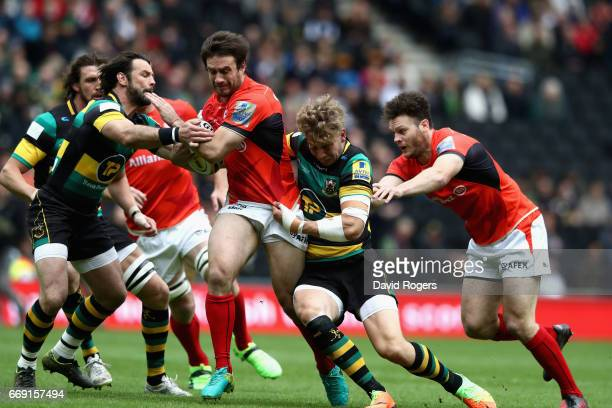 Marcelo Bosch of Saracens is tackled by Harry Mallinder and Ben Foden during the Aviva Premiership match between Northampton Saints and Saracens at...