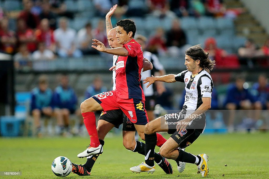 Marcelo Carrusca of Adelaide is tackled by Zenon Caravella of the Jets during the round 25 A-League match between Adelaide United and the Newcastle Jets at Hindmarsh Stadium on March 15, 2013 in Adelaide, Australia.