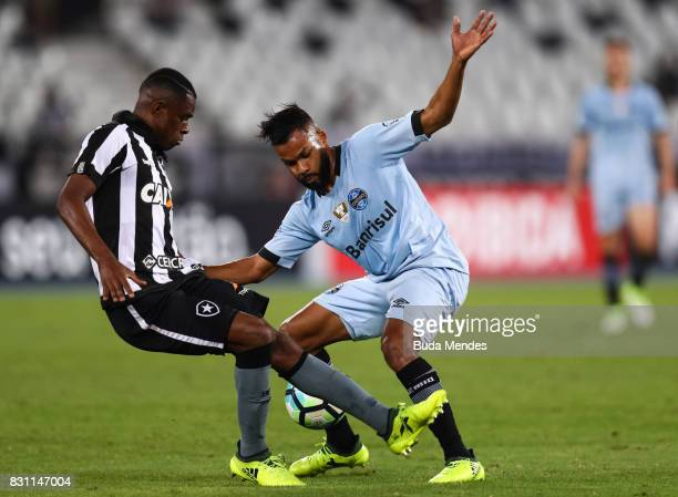 Marcelo Conceio of Botafogo struggles for the ball with Fernandinho of Gremio during a match between Botafogo and Gremio as part of Brasileirao...