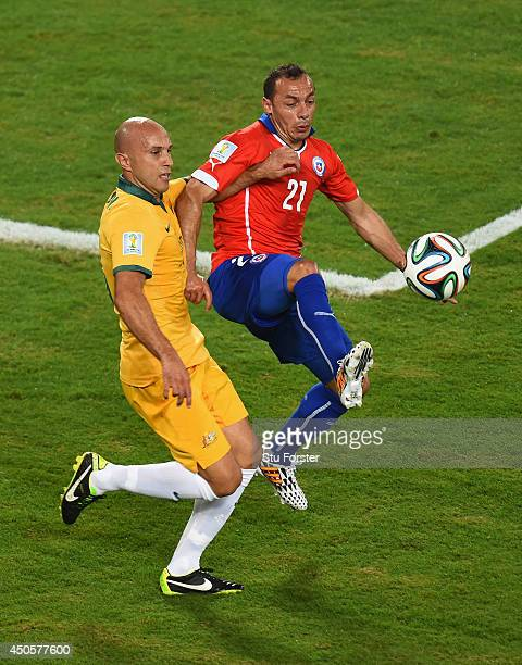 Marcelo Diaz of Chile fights off a challenge by Mark Bresciano of Australia during the 2014 FIFA World Cup Brazil Group B match between Chile and...